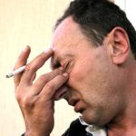 Crying brunette man with cigarette holding his eyes.
